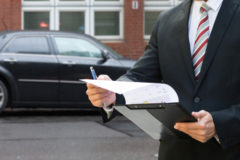 Professional,Man,Standing,In,Front,Of,Black,Car,Holding,Clipboard